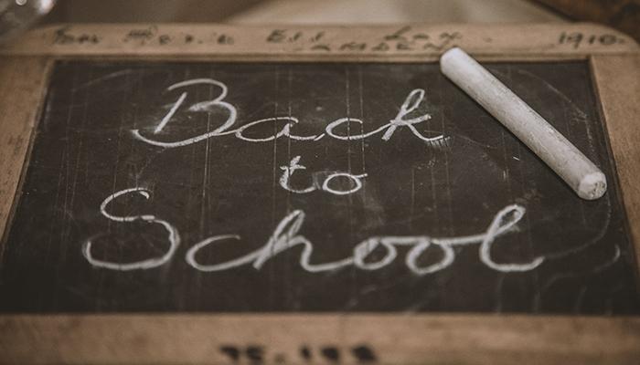 back to school written in chalk on a small hand held chalkboard